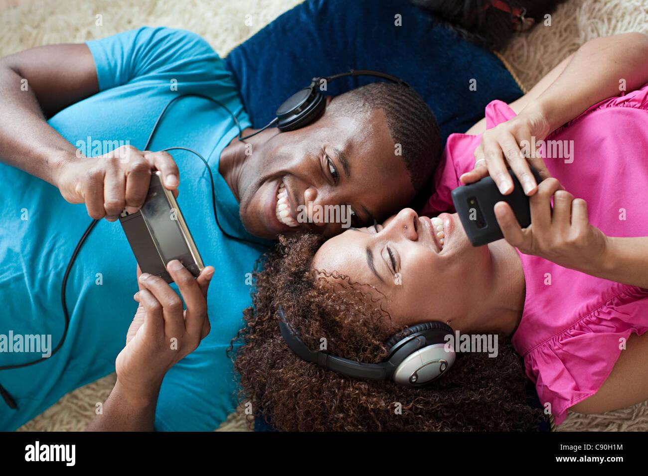 Un hombre y una mujer jugando en el dispositivo portátil y smartphone Imagen De Stock
