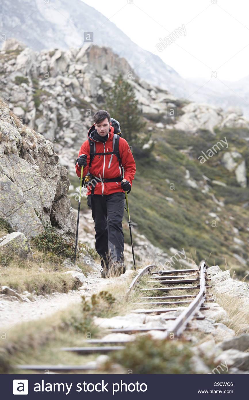 Hombre de senderismo a lo largo de antiguas vías ferroviarias, Estany Tort, Carros de Foc, Aiguestortes i Estany Imagen De Stock