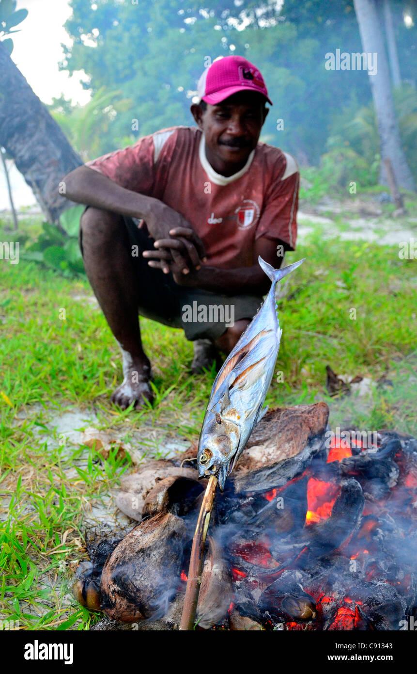 Pescador indonesio asar pescado sobre el fuego, Raja Ampat islas cerca de Papúa Occidental, Indonesia, en el Imagen De Stock