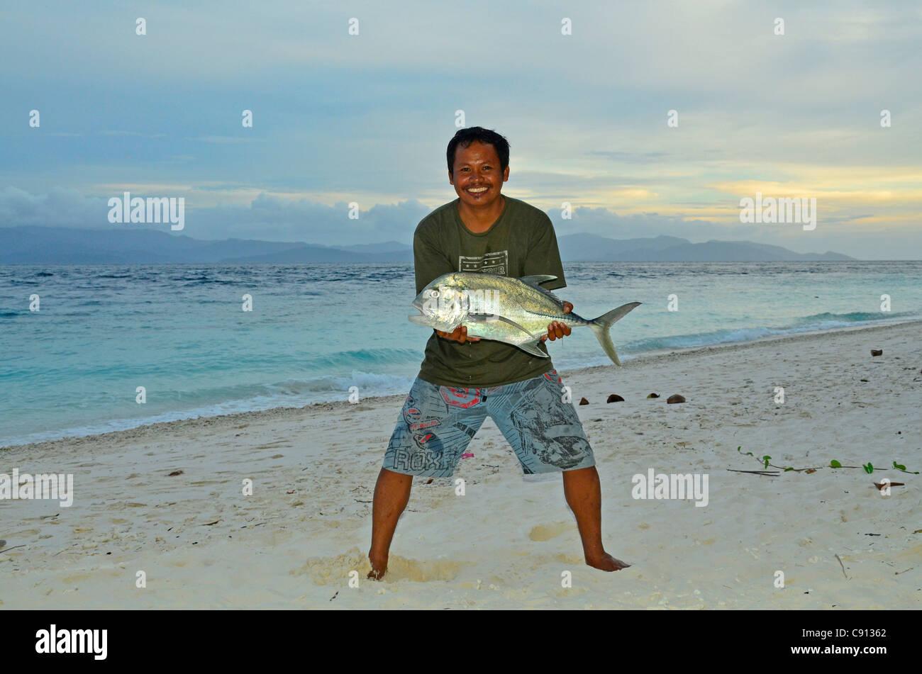 Pescadores excitados mostrando big fish en la playa, Raja Ampat islas cerca de Papúa Occidental, Indonesia, Imagen De Stock