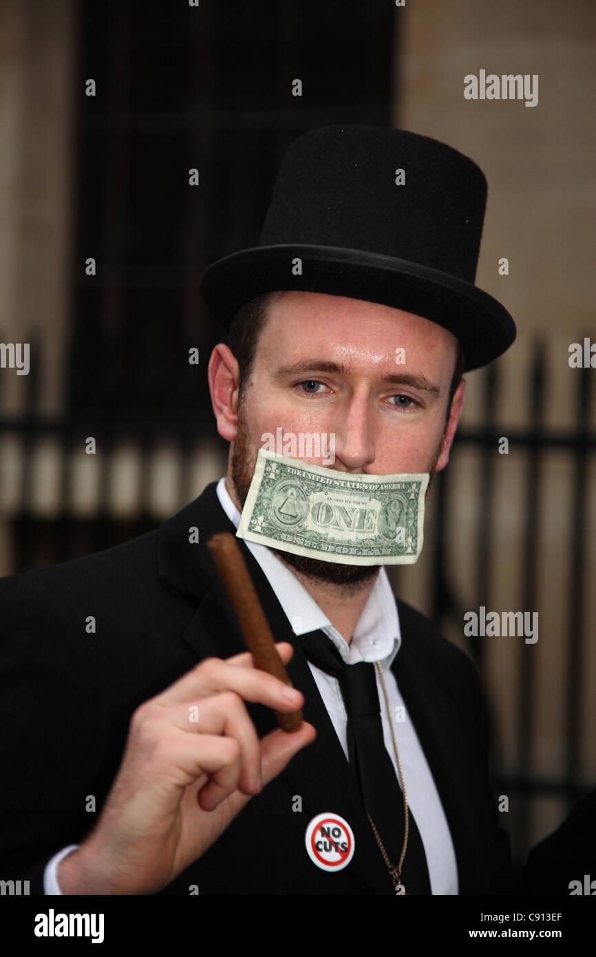 Manifestante anti capitalista con un billete de dólar atascado en su boca. Imagen De Stock