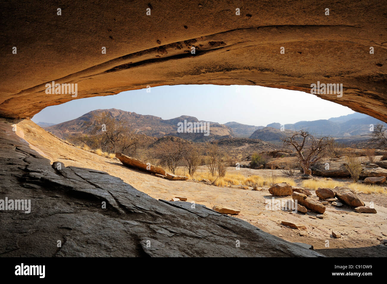 Abrigo rocoso Phillipp's Cave con vistas a Savannah, Ameib, montañas Erongo, Namibia Foto de stock