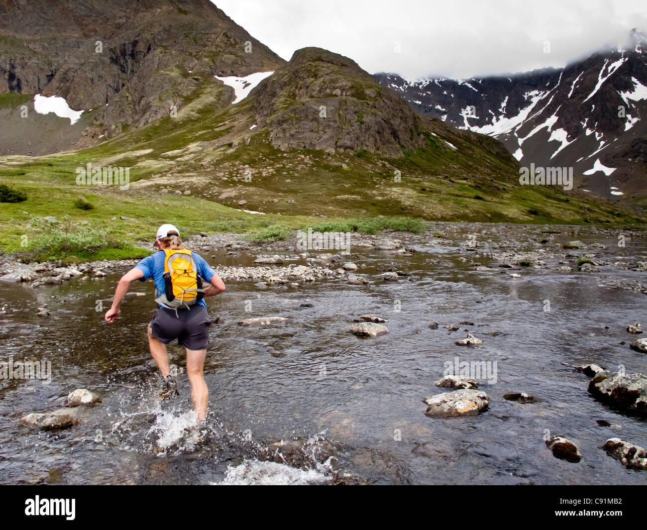 Trail Runner salpica a través de la Bifurcación Medio Campbell Creek mientras ejecuta el Monte Elliot Imagen De Stock