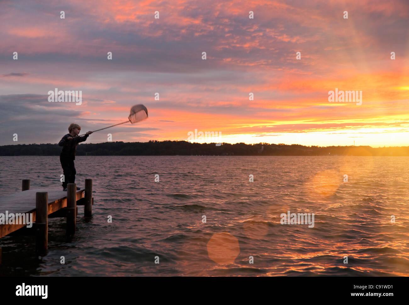 Chico pesca con red en el lago Foto de stock
