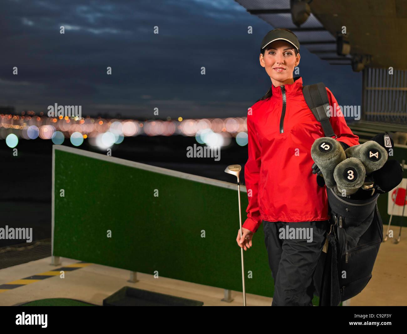 Mujer con palos de golf en el driving range Foto de stock