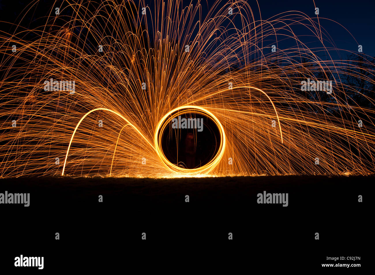 Hilado de lana de acero, creando hermosas vetas circular de luz dorada de la quema de lana de alambre dentro de un batidor conectado al cable o cuerda. Foto de stock
