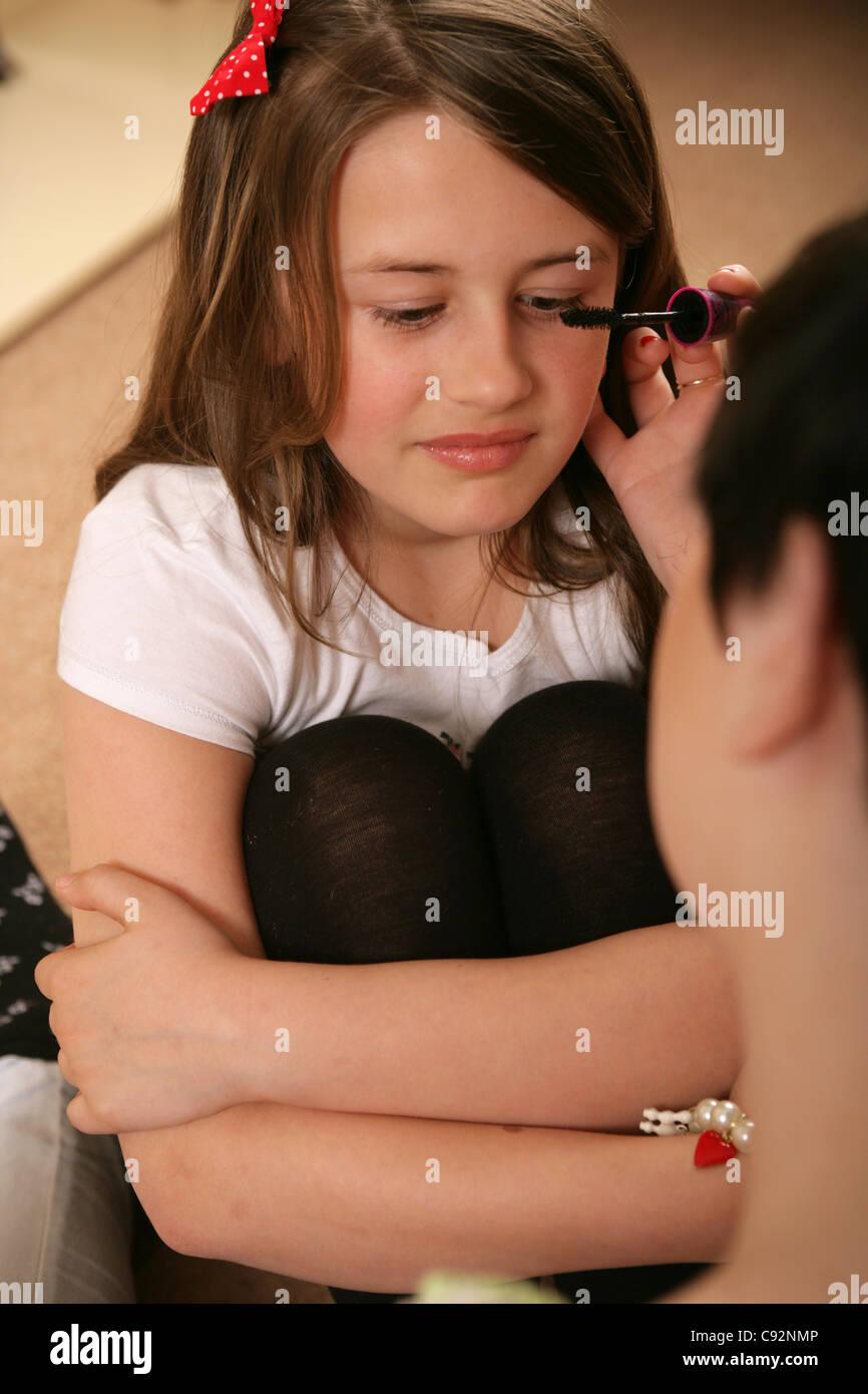 Una hermana mayor de aplicar el rímel a su hermana menor. Imagen De Stock
