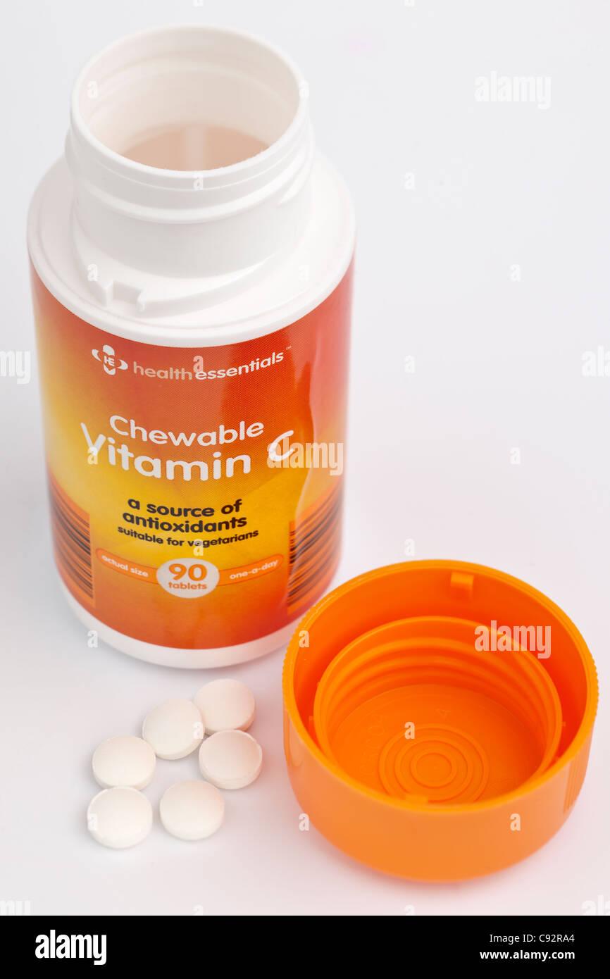 Las tabletas masticables de vitamina C con un día de health essentials 90 en un recipiente de tapón de Imagen De Stock