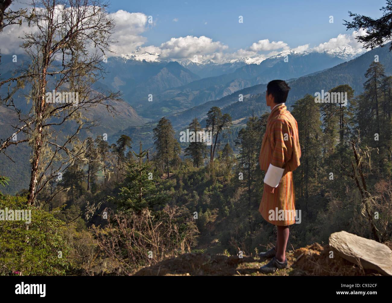 Un hombre bhutaneses en traje opiniones de una de las montañas del Himalaya desde las montañas Negras Imagen De Stock