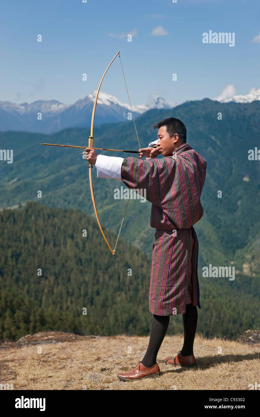 Tiro con arco, datse, es un deporte nacional favorito de los butaneses. Aquí un arquero sus habilidades prácticas Foto de stock