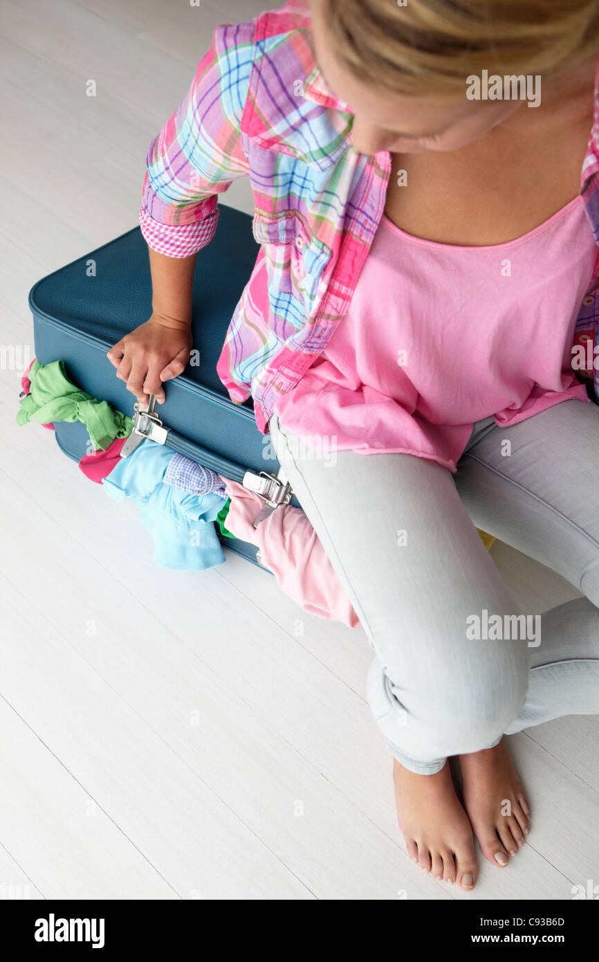 Adolescente luchando para cerrar maleta Foto de stock