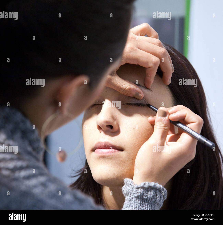 Una adolescente con mascara ojo aplicado por un artista de maquillaje Imagen De Stock
