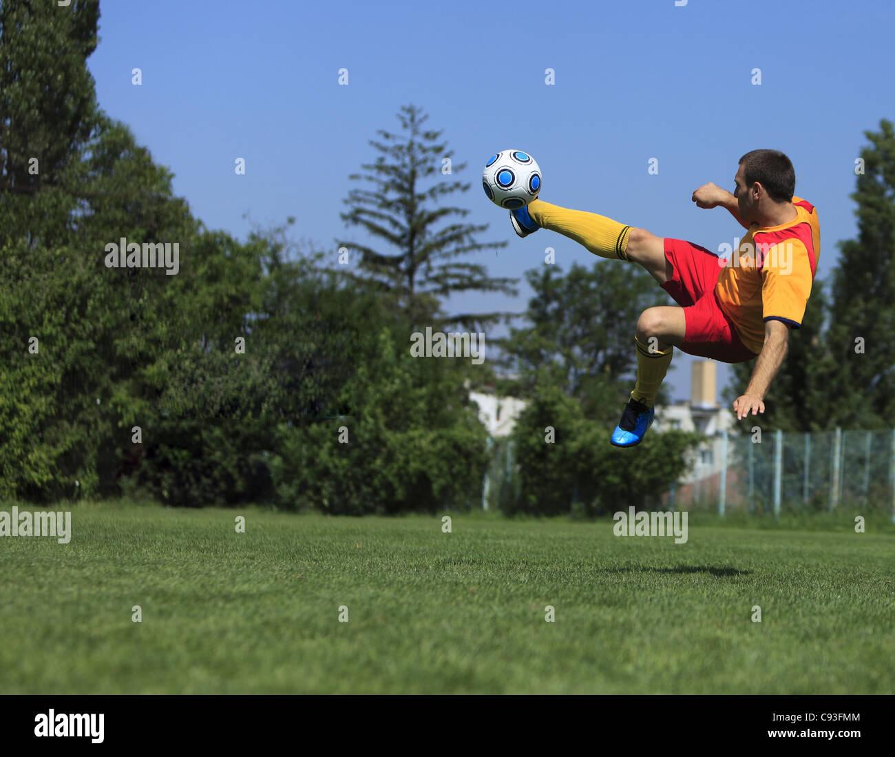 Un jugador de fútbol patear el balón en una posición acrobática. Foto de stock
