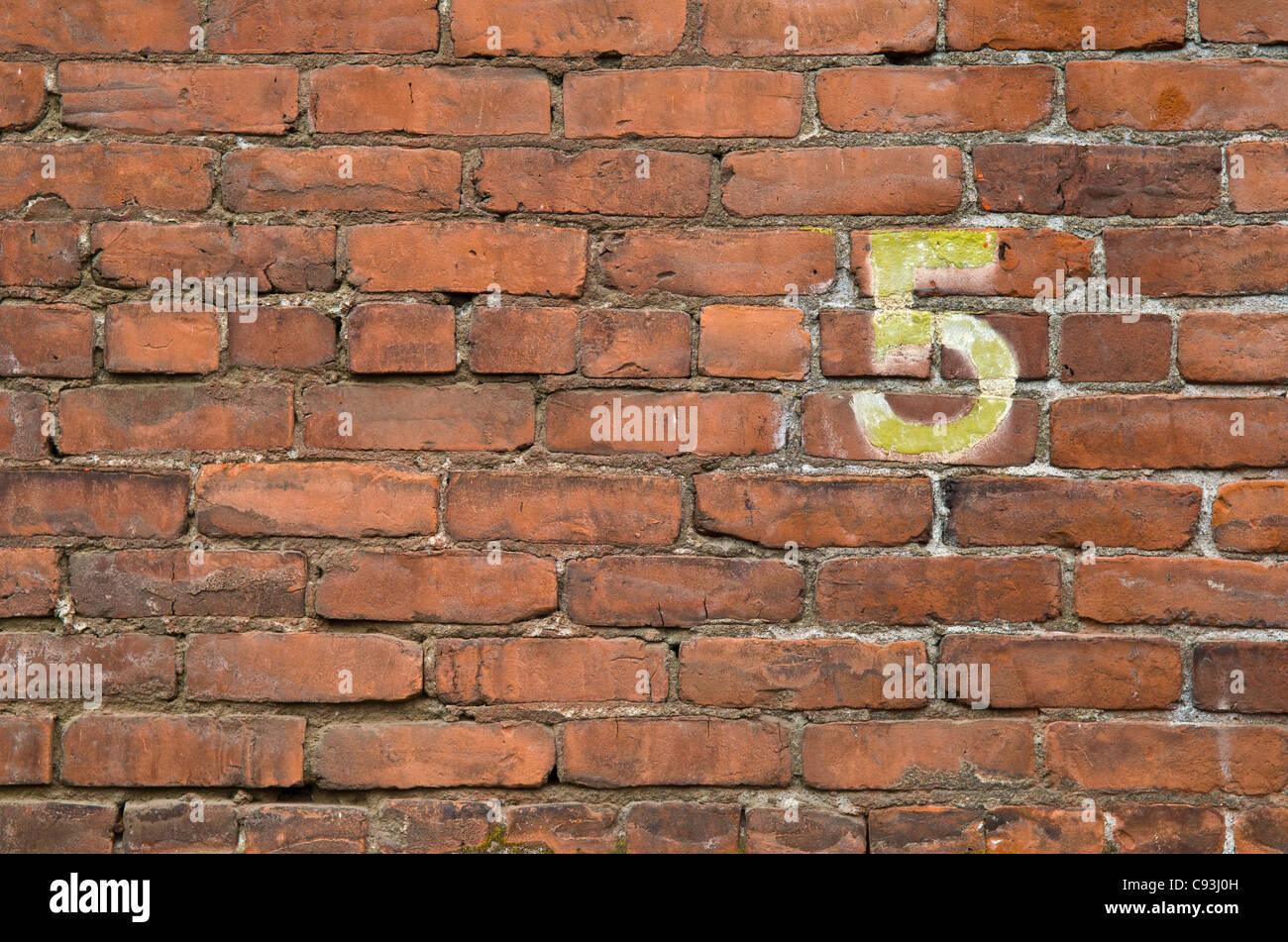 El número 5 pintado sobre una pared de ladrillos en el barrio Pearl de Portland, Oregon. Imagen De Stock