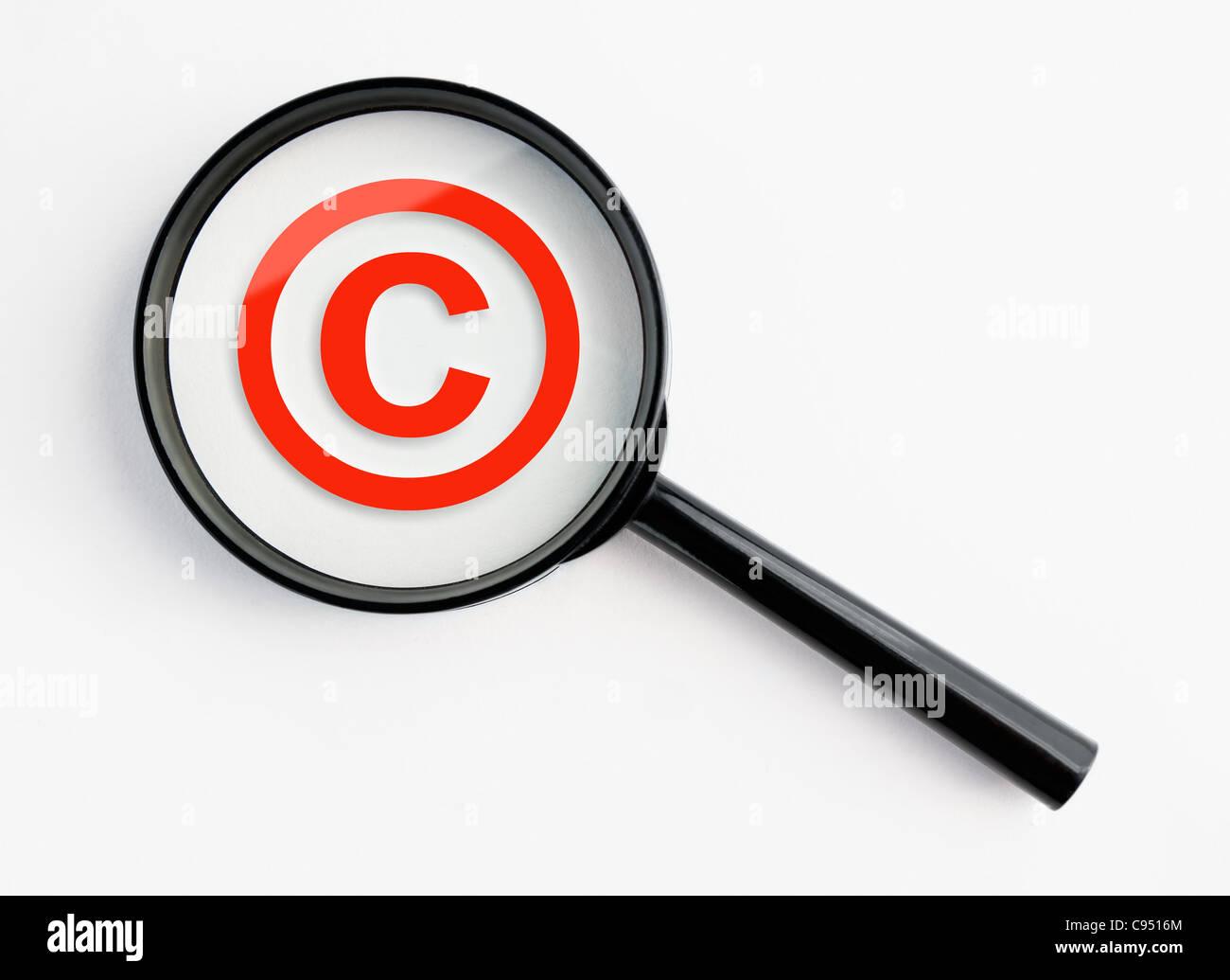 Símbolo de copyright bajo una lupa, con aislados antecedentes Foto de stock