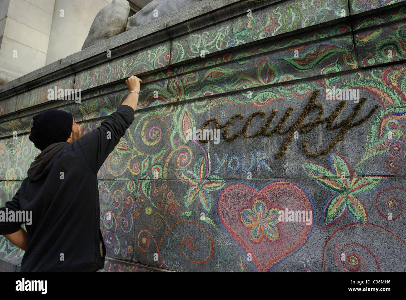 Manifestante creando arte con tiza de color en las paredes de granito de la galería de arte de Vancouver. Imagen De Stock