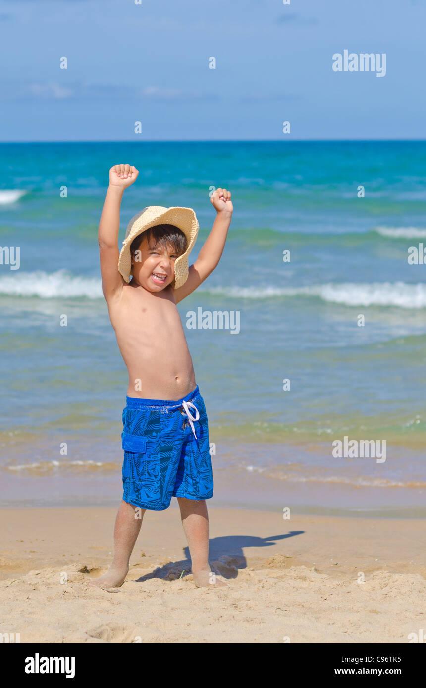 Alegre chico con sombrero alza los brazos y gritando en la playa Imagen De Stock