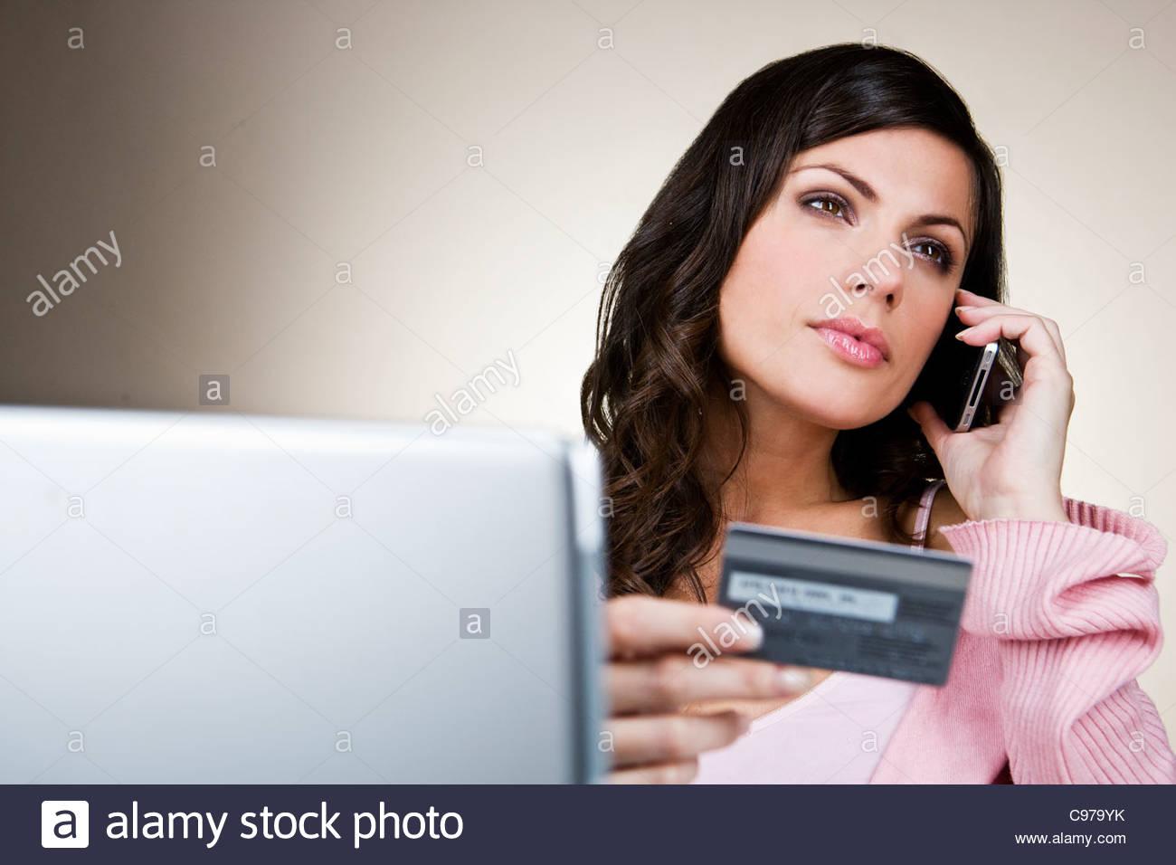Una joven mujer en el teléfono, sosteniendo su tarjeta de crédito Imagen De Stock