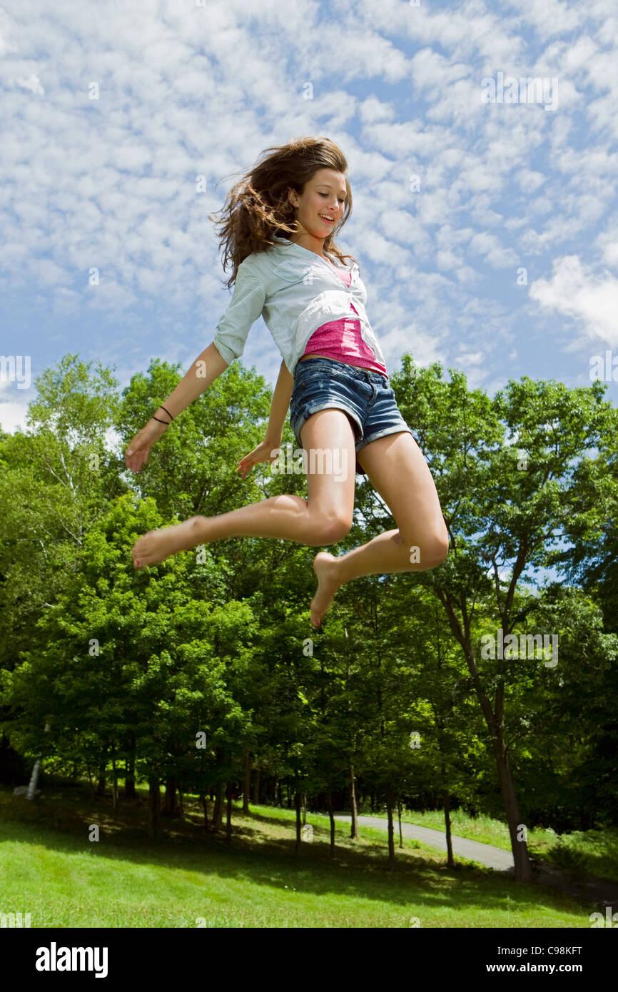 Adolescente rebotando campiña alta de aire Imagen De Stock