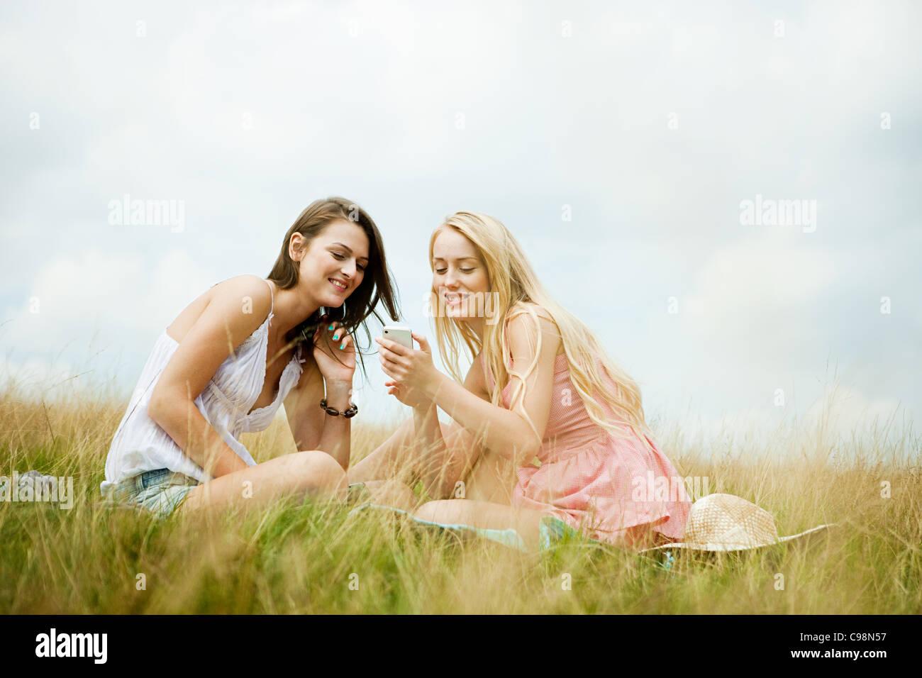 Las mujeres jóvenes que buscan conjuntamente dispositivos de mano Imagen De Stock