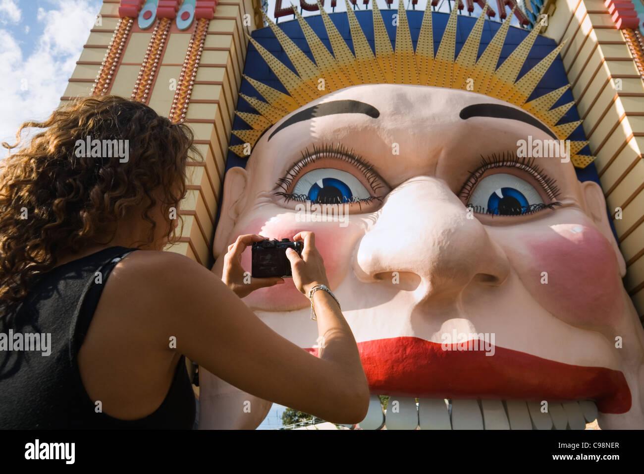 Una mujer fotografía la cara sonriente de Luna Park - Sydney histórico del parque de diversiones. Sydney, Imagen De Stock