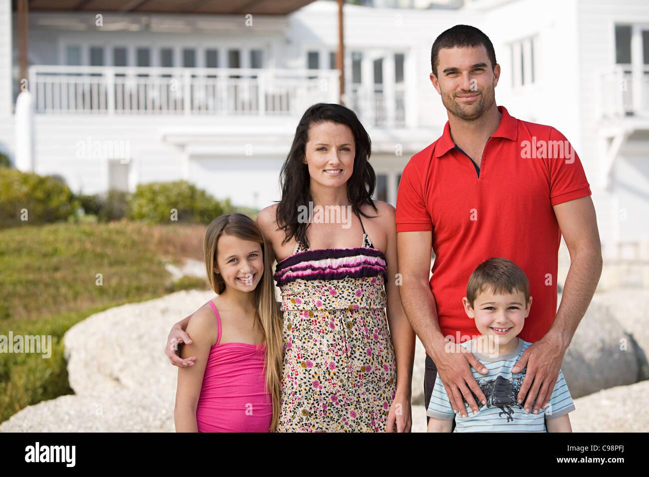 Familia de pie junto a la foto de grupo de vacaciones Foto de stock