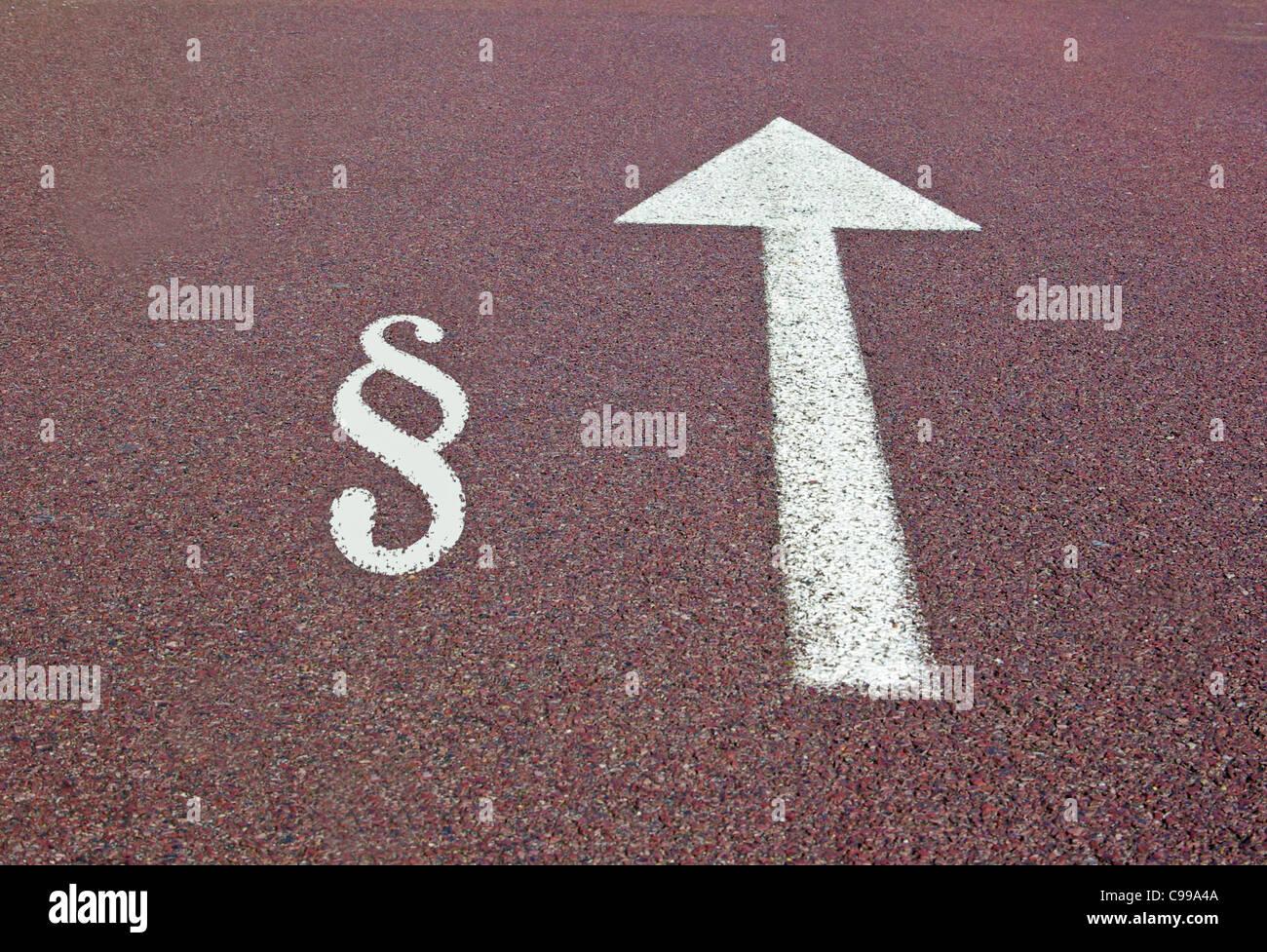 Una flecha en el asfalto mostrando la dirección con la ley firmar cerca Foto de stock