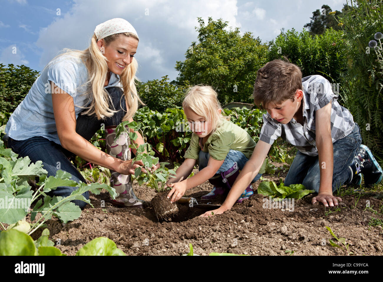 Alemania, Baviera, Altenthann, mujer e hijos juntos en jardinería jardín Foto de stock