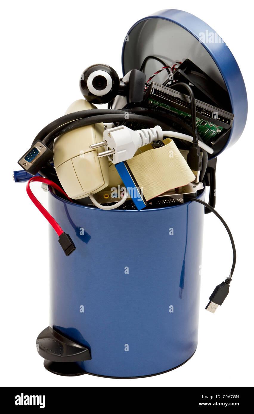 Pequeño cubo de basura con residuos electrónicos sobre fondo blanco. Imagen De Stock