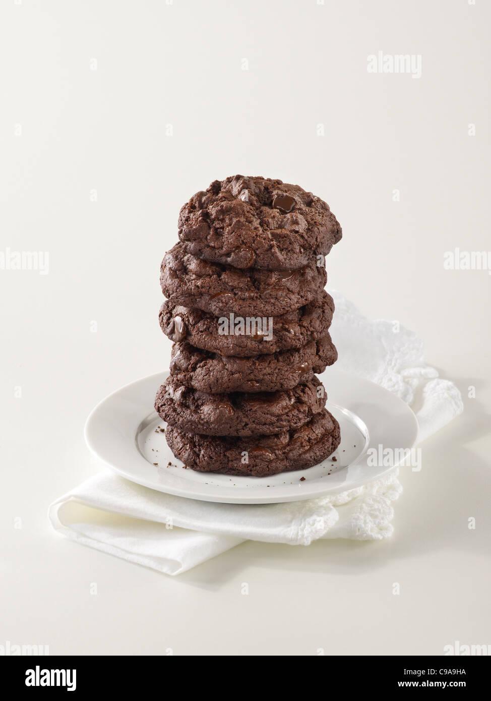 Una pila alta de triple gourmet chocolate chip cookies en una placa blanca. Foto de stock