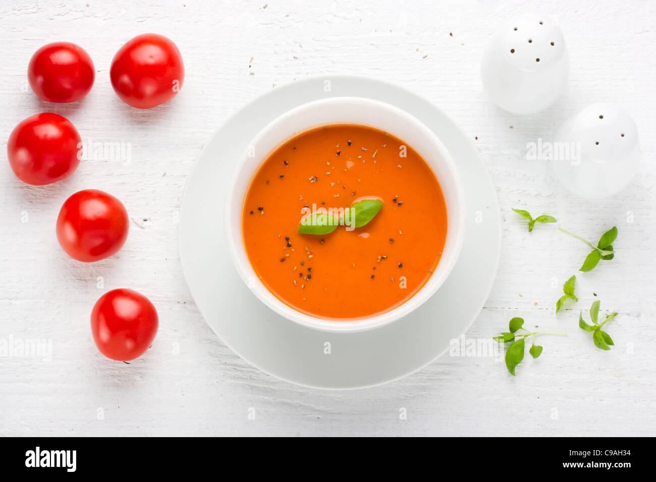 Sopa de tomate en el recipiente blanco rodeado con tomate y albahaca sal Pepper Shaker imagen tomada desde arriba Imagen De Stock