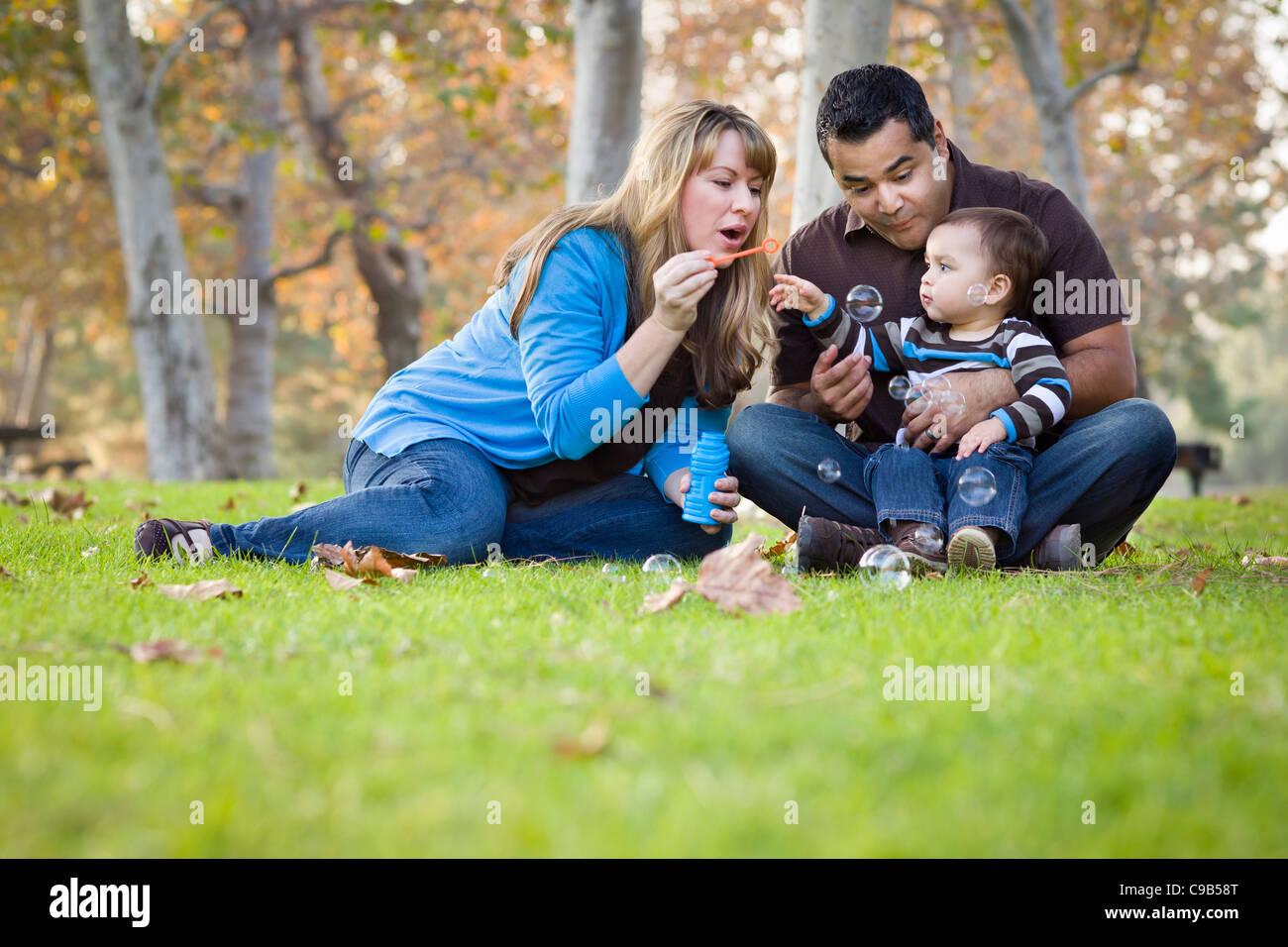 Feliz joven de raza mixta familia étnica jugando con burbujas en el parque. Imagen De Stock