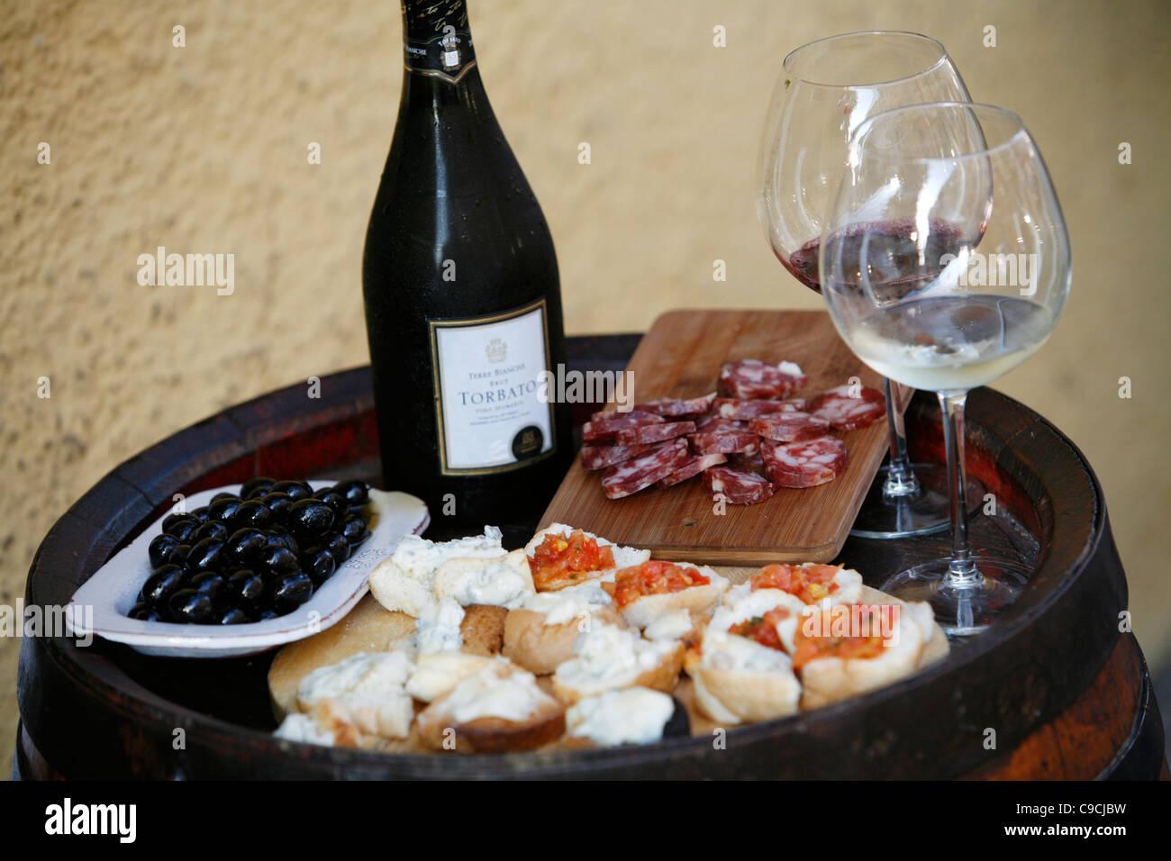 Plato de queso, salami, aceitunas y vino en Osteria da Lio, La Maddalena, Cerdeña, Italia. Imagen De Stock