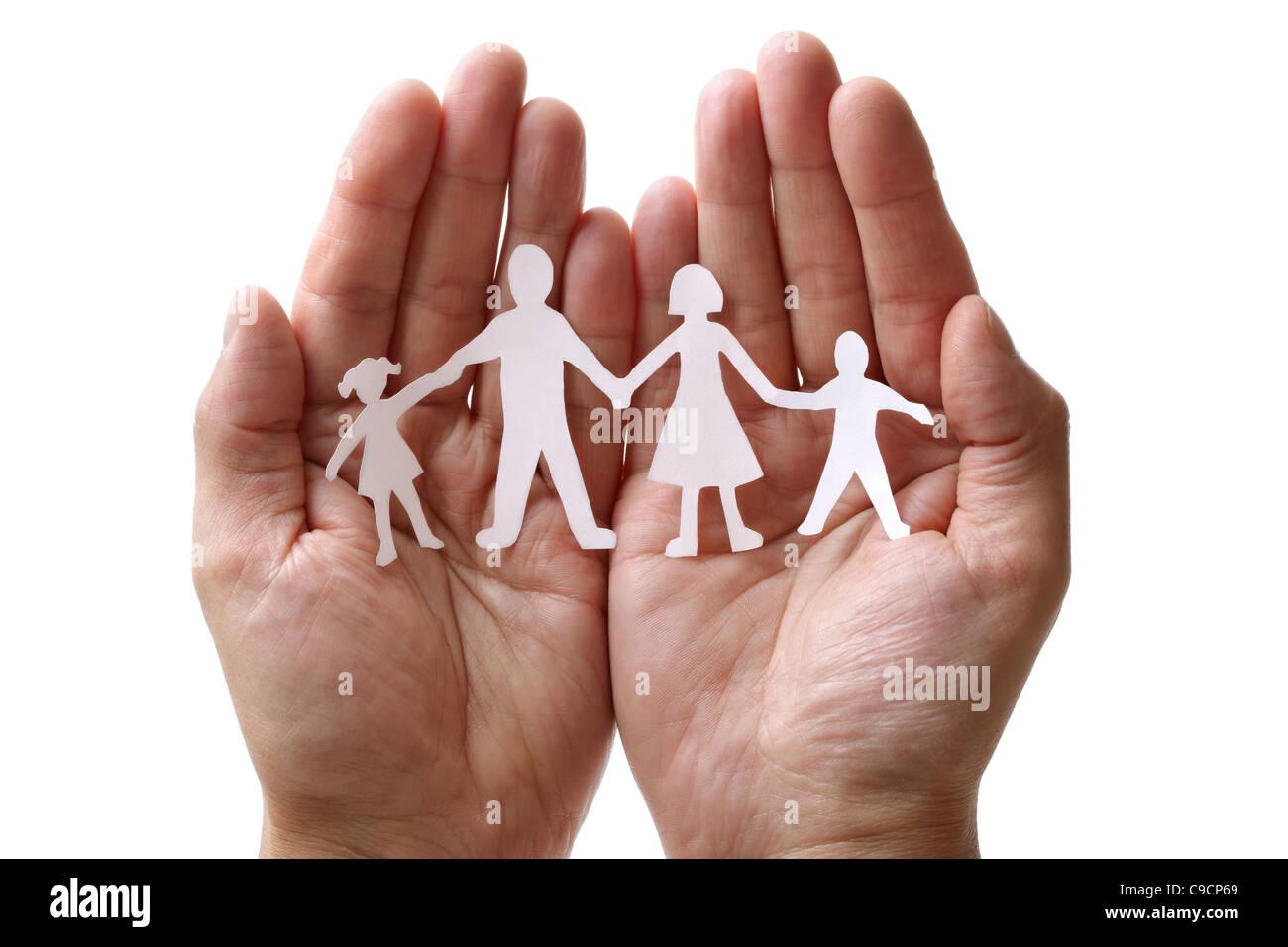 Cadena de papel familia protegida en manos ahuecados Imagen De Stock