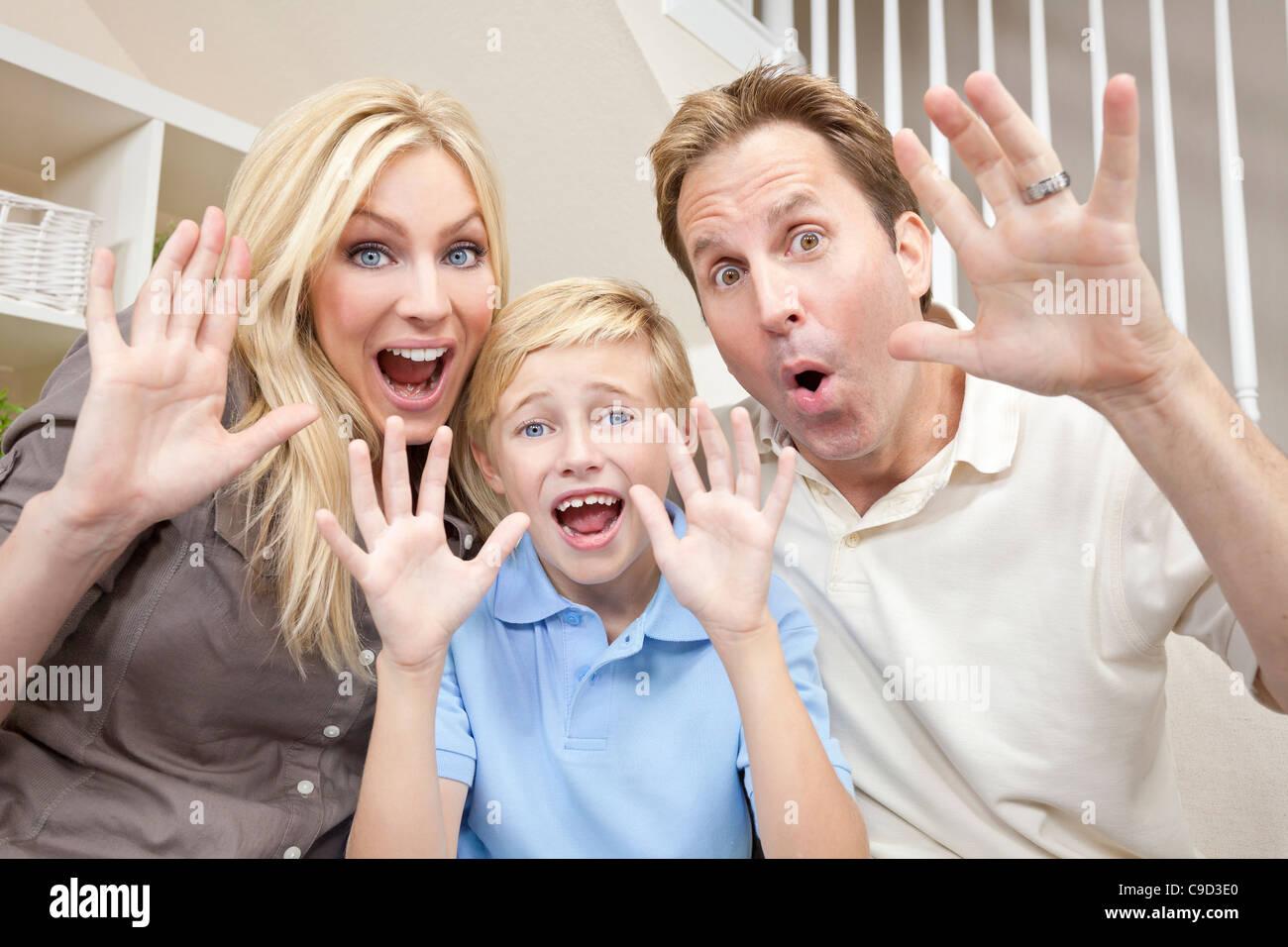 Un atractivo de la familia feliz, la risa de la madre, el padre y el hijo está sentado en un sofá en casa divertirse Foto de stock