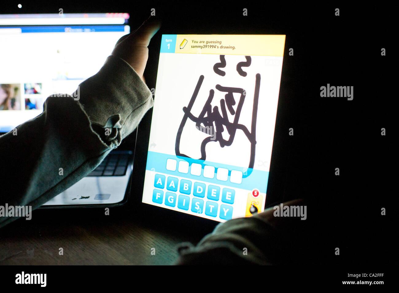 El 25 de marzo de 2012: una niña de 13 años utilizando la app dibujar algo sobre un nuevo Apple iPad 3 Tablet PC. Un pequeño OMGPOP, juegos basados en Nueva York empresa acaba de ser comprada por $180m (£113m) después de lanzar la app que fue descargado 35 millones de veces en las últimas seis semanas. Foto de stock