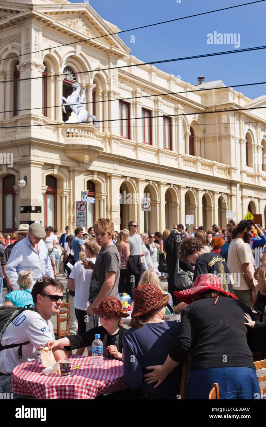 High Noon es un festival comunitario local Northcote Music Fest en Melbourne, Australia, la familia gozan de una mesa de café en la calle. Foto de stock