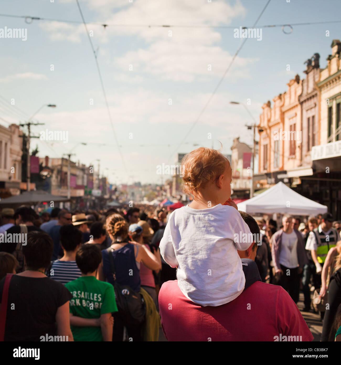High Noon es un festival comunitario local Northcote Music Fest en Melbourne, Australia, el niño obtiene un piggy back a través de la multitud. Foto de stock