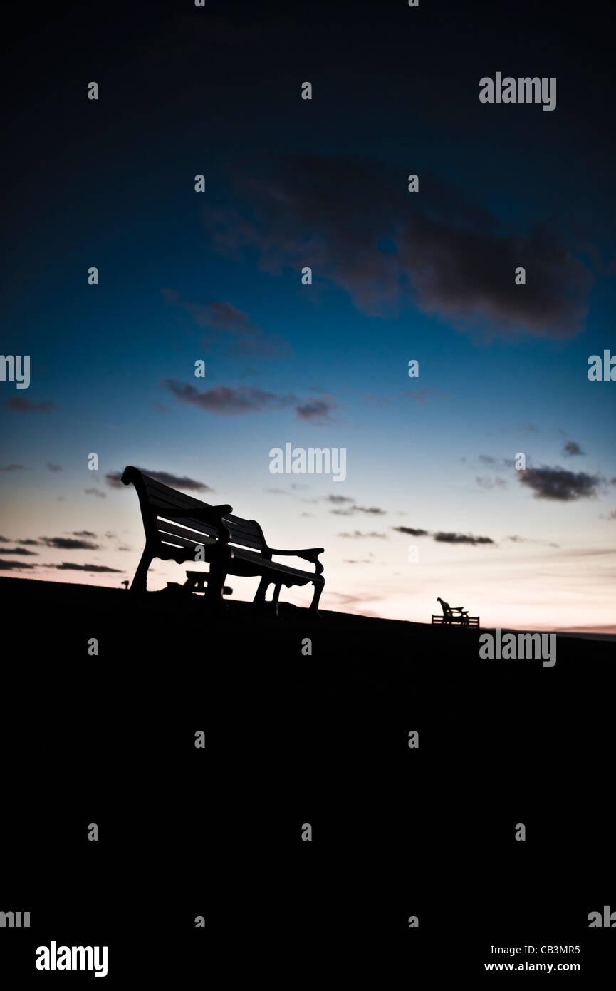 Siluetas de vaciar los bancos del parque contra el horizonte de un cielo crepuscular, REINO UNIDO Imagen De Stock