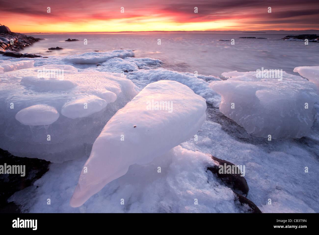 Colorida tarde y formaciones de hielo en Nîmes en la isla Jeløy en Moss kommune, Østfold fylke, Noruega. Imagen De Stock