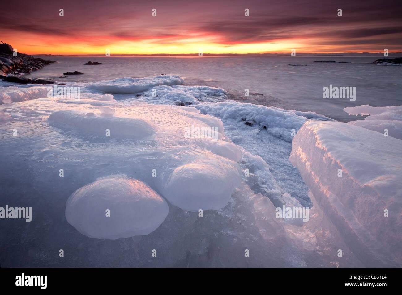 Colorida tarde y formaciones de hielo en Nîmes en la isla Jeløy, Moss kommune, Østfold fylke, Noruega. Imagen De Stock