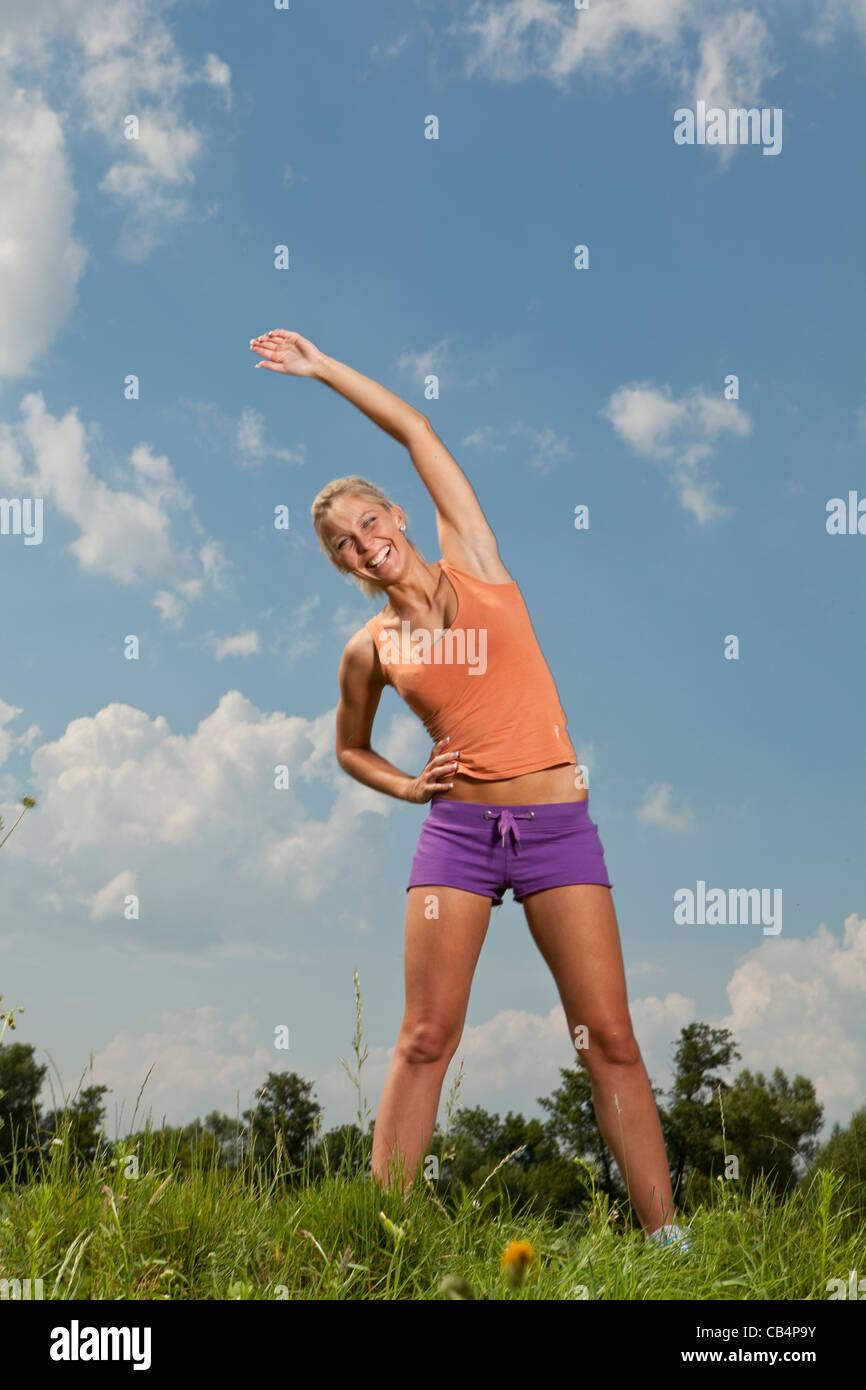 Chica rubia en la naturaleza parque verde, un programa de acondicionamiento físico Imagen De Stock