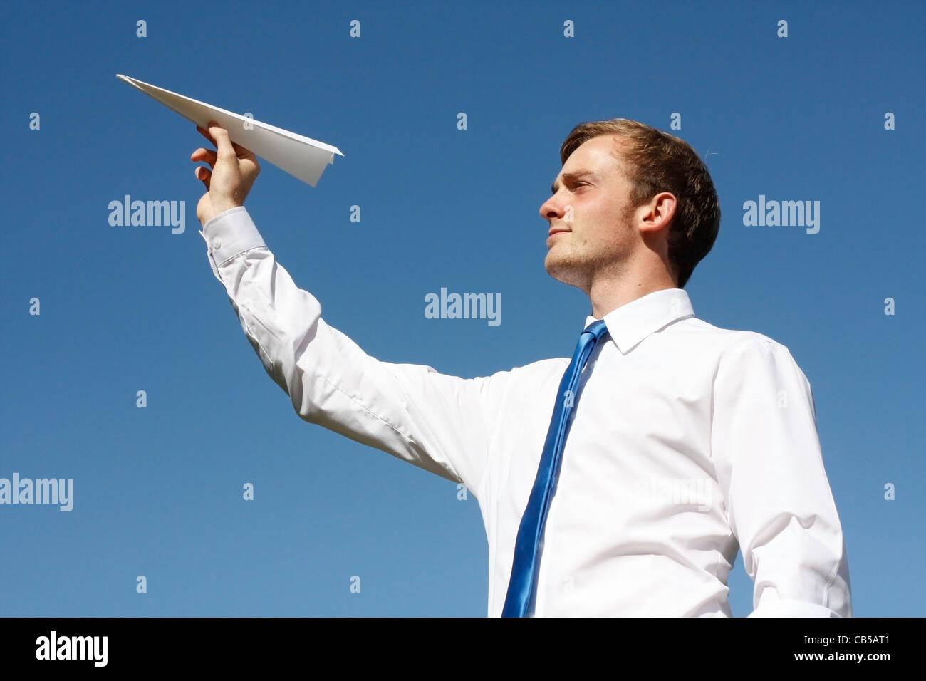 Un hombre de negocios lanzando un avión de papel Imagen De Stock