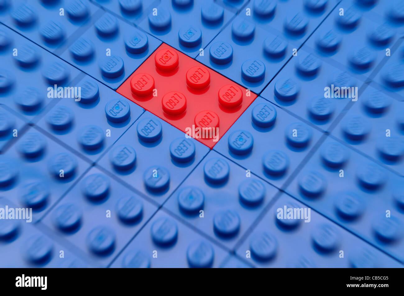 Un único edificio de ladrillo rojo de juguete azul destaca entre los ladrillos del edificio. Imagen De Stock
