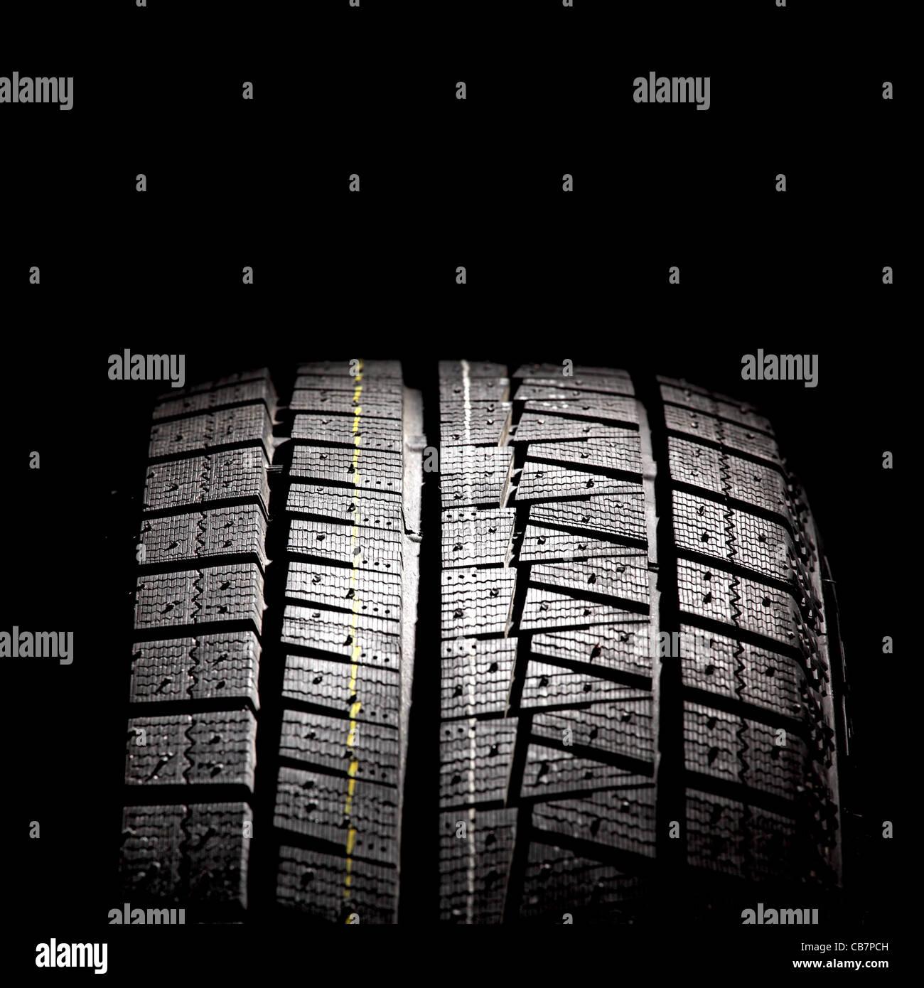 Parte del nuevo neumático de coche aislado sobre un fondo negro. Formato cuadrado. Foto de stock