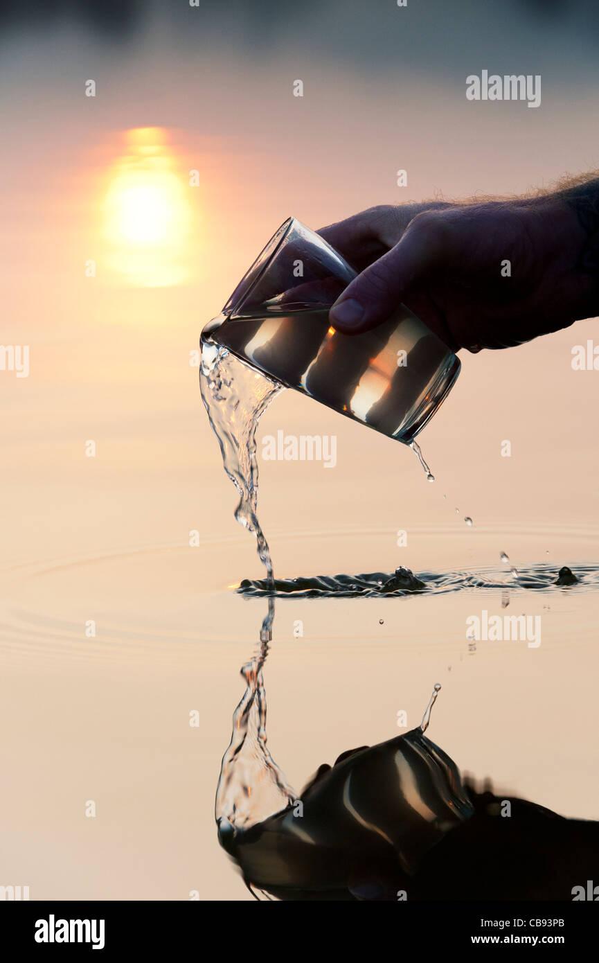 Verter agua de un vaso en un lago al amanecer en la India. Silueta Imagen De Stock
