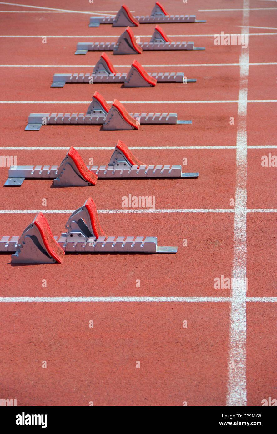 Los bloques de arranque de atletismo en una pista de atletismo de color rojo en el estadio. Imagen De Stock