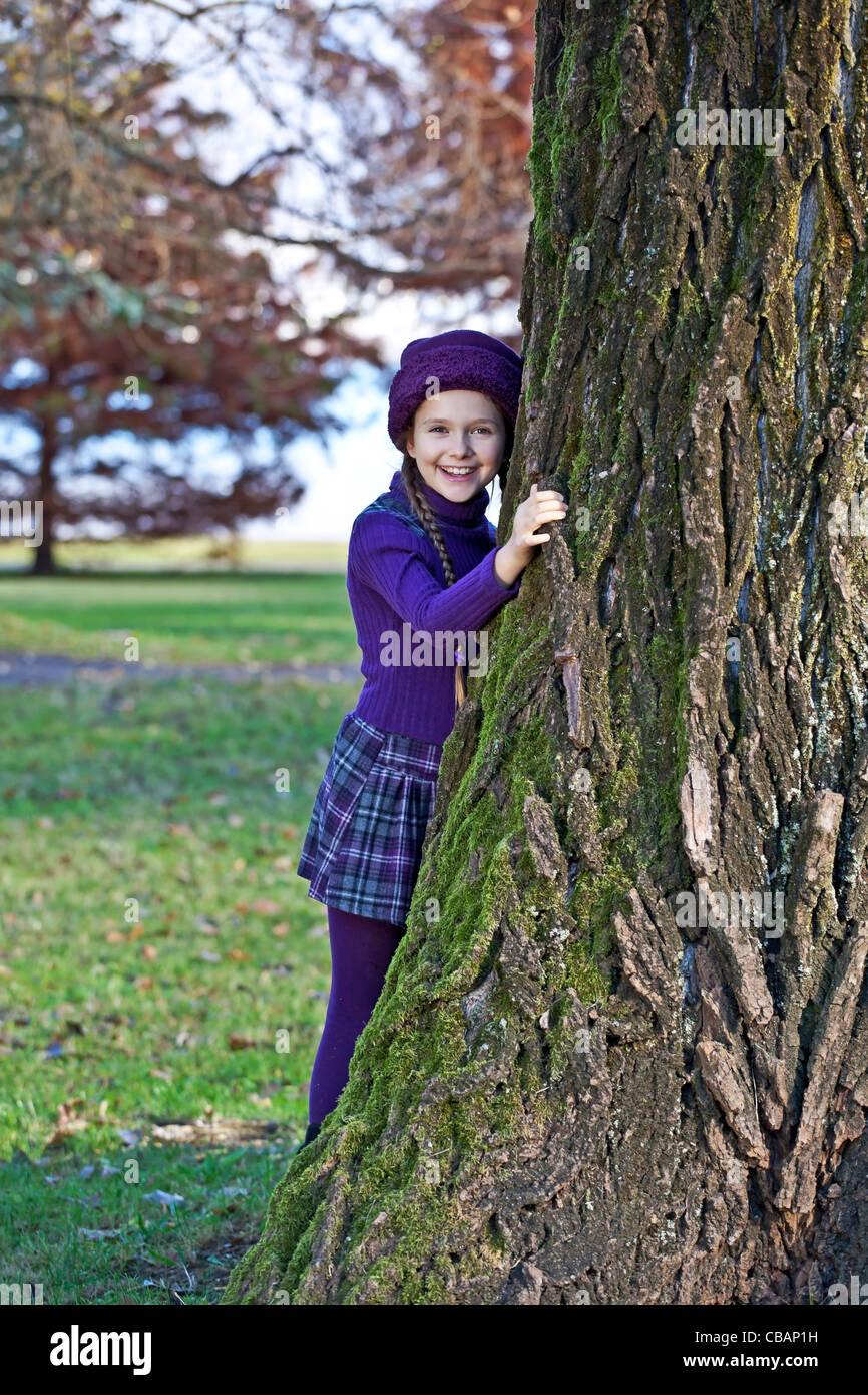 Chica se inclina en otoño en un parque sobre el tronco de un árbol. Imagen De Stock