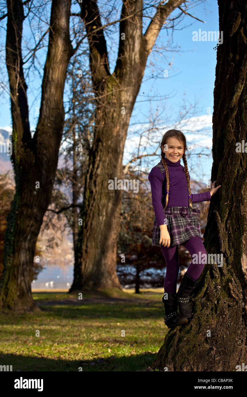 Chica escalada en otoño en un parque sobre el tronco de un árbol Imagen De Stock