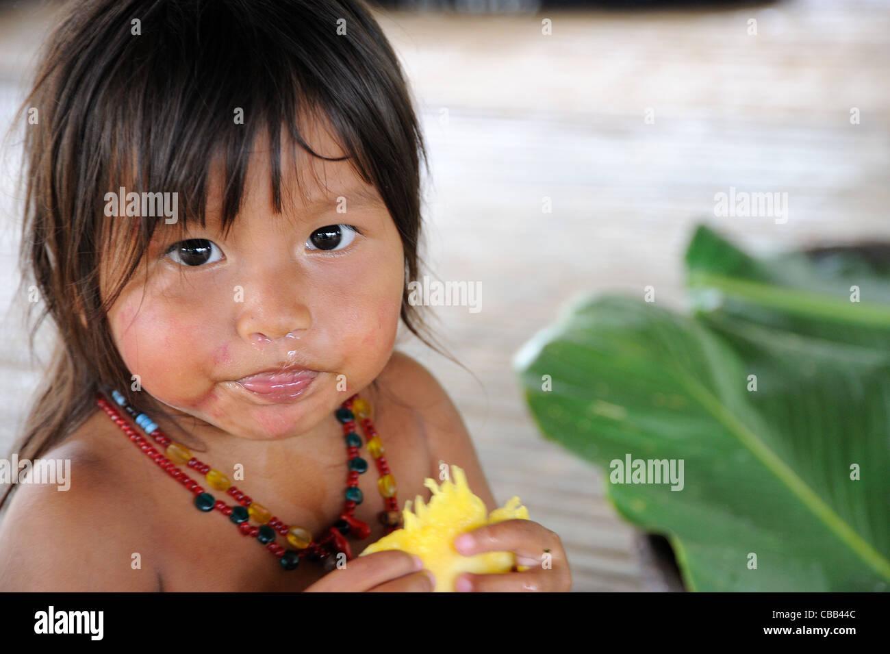 Niña indígena Embera comiendo piña y soltando el moco en la comunidad indígena Embera Puru, Panamá Foto de stock